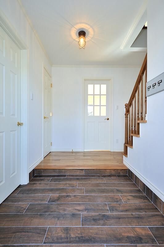 雰囲気たっぷりのウッド調タイルを使用した玄関ホール